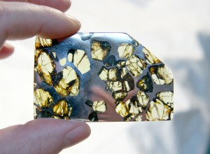 The Esquel pallasite. The presence of olivine grains in a metal matrix is thought to represent mixing of the mantle with the core from a catastrophic impact. (Image from Wikipedia)